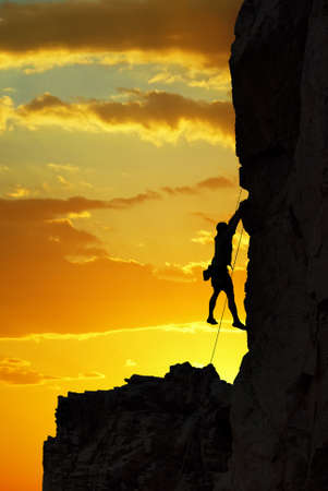 intrinsic: Man rock climber silhouette over bright sunset