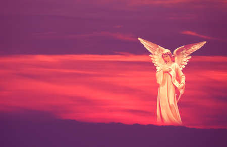 Beautiful angel over pink and purple sky background concept of religion Фото со стока