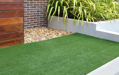 Combination of timber, plants, rocks, artificial grass, brick and render wall  Banque d'images