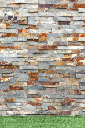 stacked stone: Stacked Stone Cladding covers wall exterior details with grass Stock Photo
