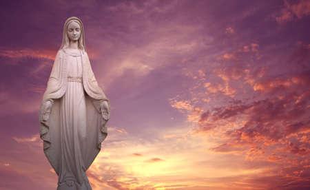 Statua della Vergine Maria su sfondo tramonto concetto di religione