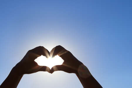 shape silhouette: Silhouette of wet hands in heart shape with sun in the middle