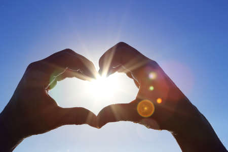 shape silhouette: Silhouette of wet hands in heart shape with sunning sun