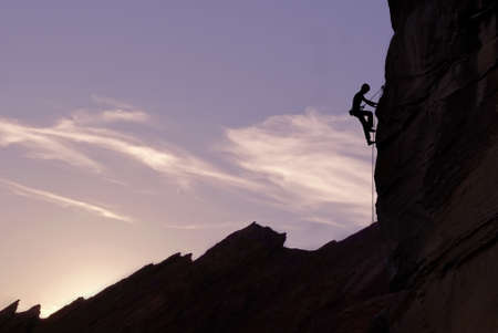 intrinsic: Man rock climber silhouette over bright sun background