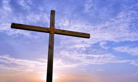 Houten kruis bij zonsopgang of zonsondergangconcept godsdienst
