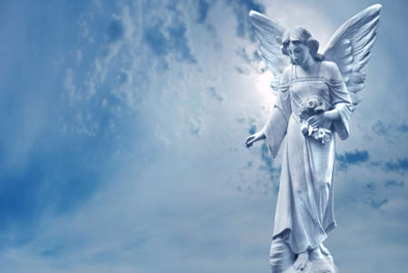 Angel sculpture on blue sky background concept of Religion Stock Photo