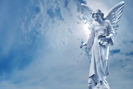 Angel sculpture on blue sky background concept of Religion Foto de archivo