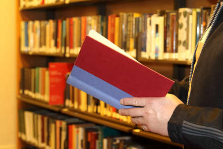 Male student reading book in library educational concepts