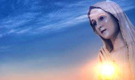 Statue of the Virgin Mary over shining sun