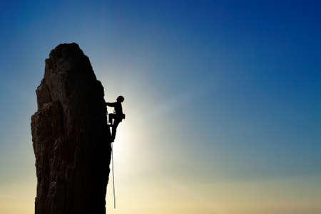 Man rock climber silhouette over bright sky background