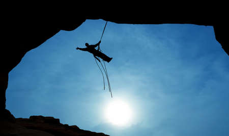 Man rock climber silhouette over blue sky background Stock Photo
