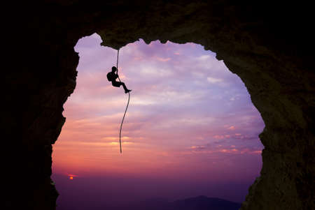 Man rock climber silhouette over bright sunset