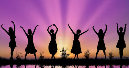 Silhouettes of beautiful young women at sunset with social distancing during pandemic