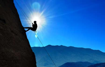 Rock climber silhouette over blue sunny sky