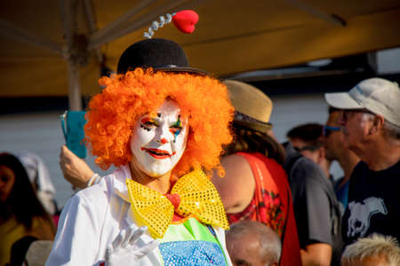 PUERTO DE LA CRUZ, SPAIN - FEBRUARY 29, 2020: The official end of the Carnival. Marching carnival groups, dancing, decorated cars and Carnival queens. Clown among other clowns