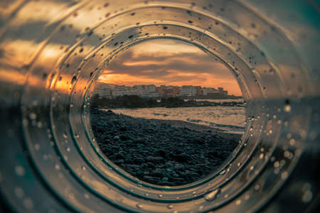 Plastic, transparent tunnel through which you can see the beach at sunset