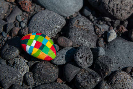 Dark stones with an emphasis on a small hand-painted stone with many colors Stock Photo