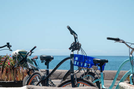 Stopped bicycles on the street in front of the sea Foto de archivo