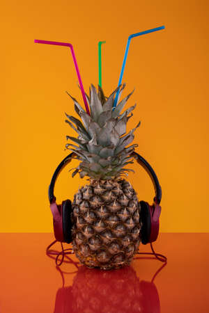 Pineapple with headphones on a colored background
