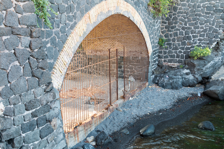 stone of destiny: tunnel with mettallic gate on the beach