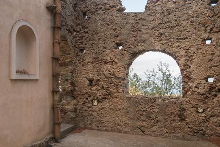 Ancient stone window That shows part of landscape photo