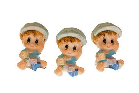 three children made of porcelain on white background photo