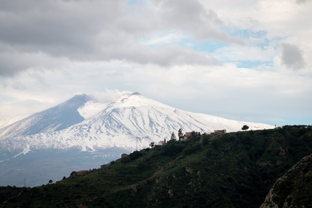 Etna snowy viewed from Taormina in a cloudy day Foto de archivo