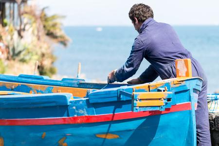 fisherman takes care of his wooden boat Foto de archivo