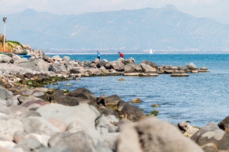 boys playing on the rocks near the sea