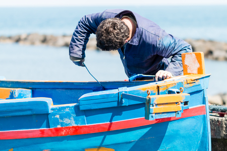 wooden boat: fisherman takes care of his wooden boat Stock Photo