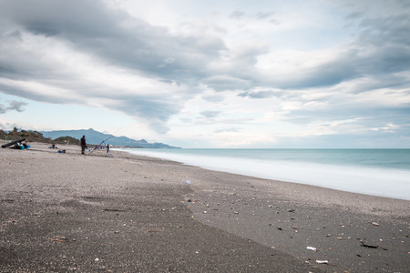 Beach with fisherman and stormy sky and cloud Foto de archivo