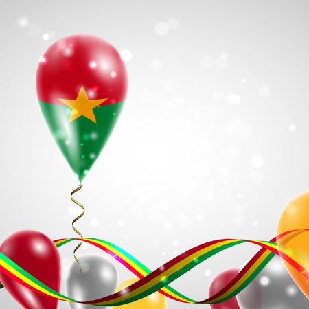 feast: Flag of Burkina Faso on balloon. Celebration and gifts. Ribbon in the colors of the flag are twisted under the balloon. Independence Day. Balloons on the feast of the national day.