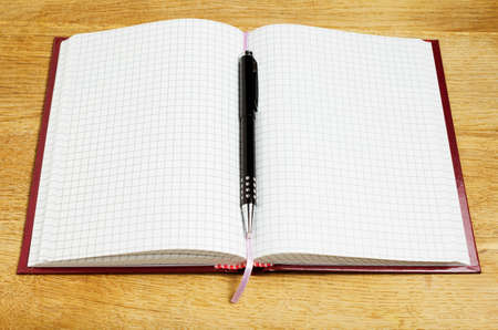 close-up of pen and notebook on wooden desk