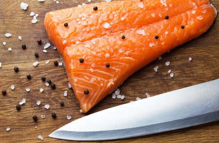 Fresh salmon fillet and knife on wooden board Stock Photo
