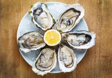 pescados y mariscos: Ostras frescas en un plato blanco con hielo y lim�n en una mesa de madera Foto de archivo