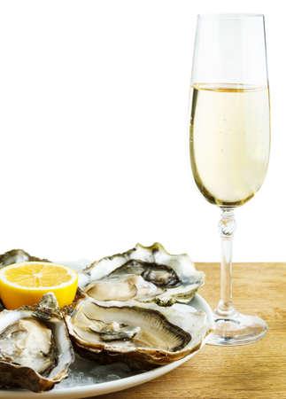 sektglas: Austern in einer weißen Platte mit Zitrone und einem Glas Wein auf einem Holztisch isoliert auf weiß Lizenzfreie Bilder