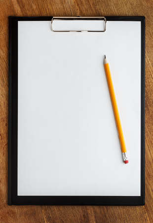 old pencil: Clipboard with pencil on a wooden desk