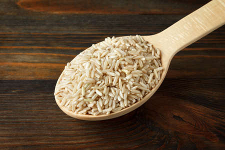unpolished: Unpolished rice in a wooden spoon on wood Stock Photo