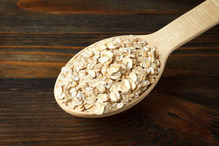 rolled oats: Rolled oats in a wooden spoon on wood