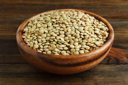 green lentil: Green lentil in a wooden bowl on wood closeup