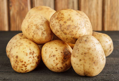 Heap of raw potatoes on wood close-up Stock Photo