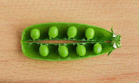 Green pea pod on wood close-up