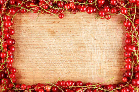 red currant: Frame made of red currant berries on wooden background