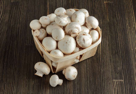 Small basket with crimini mushrooms on wood close-up