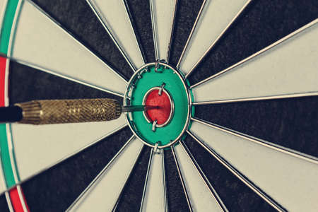 Close-up of a dart in a bullseye. Toned image