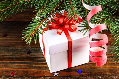 arbol de pino: Caja de regalo con lazo rojo bajo el �rbol de Navidad Foto de archivo