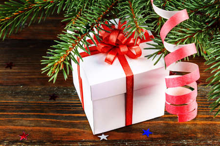 fir tree: Gift box with red bow under the Christmas tree