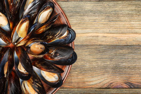 Boiled mussels in a clay dish on wood