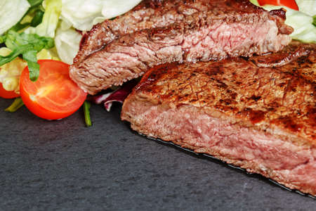 medium closeup: Close-up of medium roasted steak with salad and tomatoes on slate plate Stock Photo