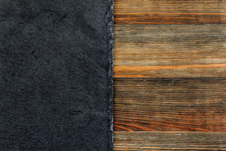 schist: Slate plate on old wooden board as a background Stock Photo